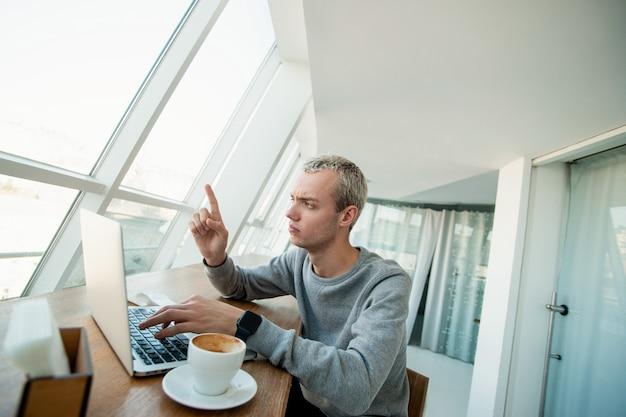 Freelancer liep vast in zijn werk. jonge geconcentreerde man in vrijetijdskleding met doorboorde neus zit voor laptop en wijst wijsvinger naar boven. witte lichte kamer op de achtergrond. lege koffiekop.