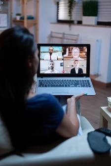 Freelancer luistert 's nachts online training op laptop zittend op een comfortabele bank