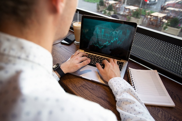 Freelancer man aan het werk op laptop in coffeeshop
