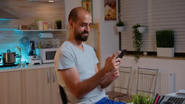 Freelancer man die telefoon gebruikt en glimlacht terwijl hij overwerkt vanuit huis. drukke, gefocuste werknemer die 's avonds laat draadloos een modern technologienetwerk gebruikt, lezen, schrijven, zoeken