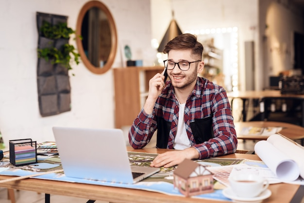 Freelancer man praten over telefoon op laptop zit aan bureau.