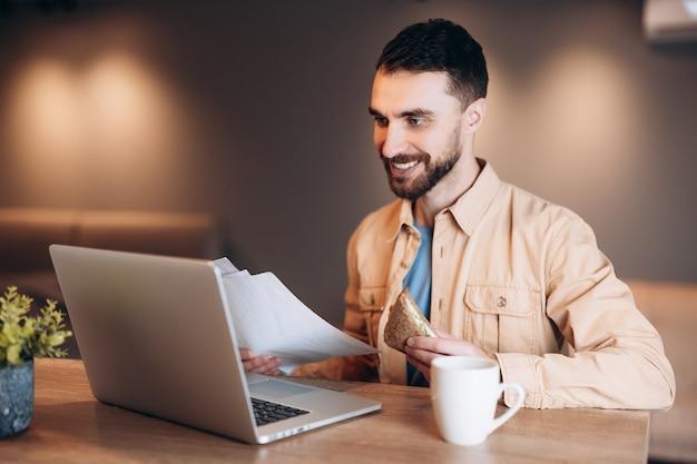 Freelancer man sandwich eten, koffie drinken en ontmoeting met baas via videocall