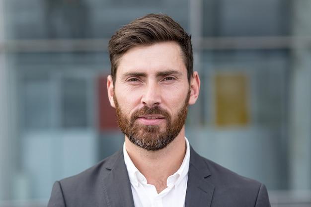 Freelancer man serieus kijken naar camera, close-up portret van een man in een pak