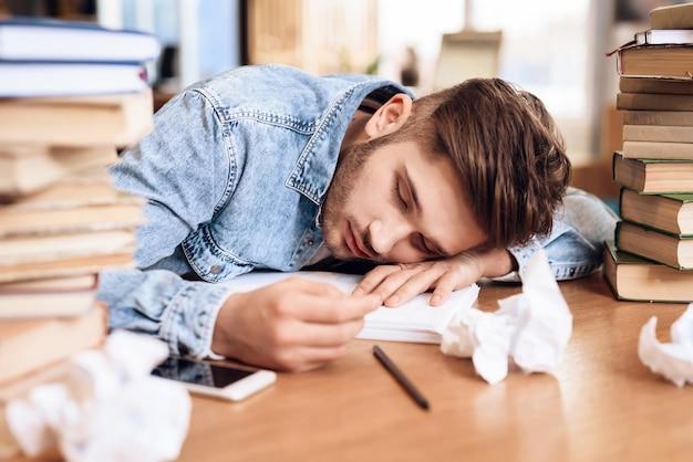 Freelancer man slapen aan bureau omringd door boeken.