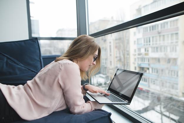 Freelancer meisje werkt voor een laptop terwijl liggend op een bank in de buurt van het raam.