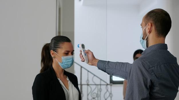 Freelancer met beschermend gezichtsmasker meet temperatuur met thermometer voordat collega's het kantoor binnenkomen. collega's die sociale afstand respecteren om besmetting met covid19 te voorkomen