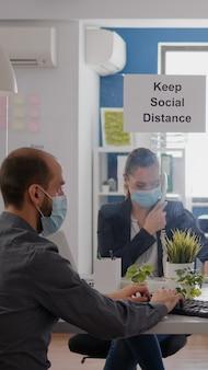 Freelancer met beschermend medisch gezichtsmasker die op een laptop werkt terwijl hij met het team telefoneert