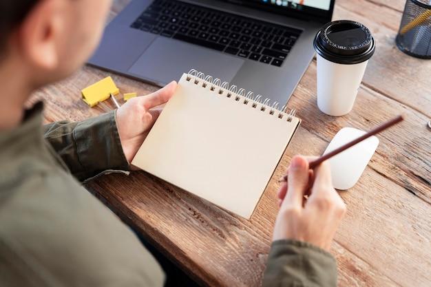 Freelancer met een hoge hoek die aantekeningen maakt