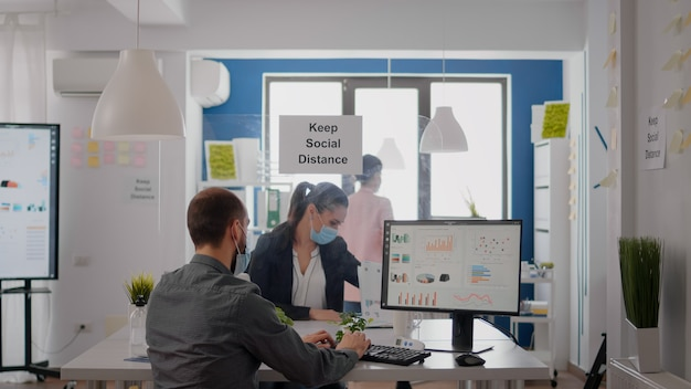 Freelancer met gezichtsmasker werken bij financiële afbeeldingen op pc zittend in kantoor. collega's die op de achtergrond praten over marketing handhaven sociale afstand om infectie met covid te voorkomen
