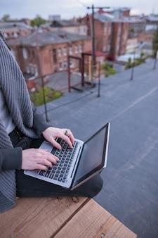 Freelancer met laptop die op hemel kijkt. onherkenbare vrouw zittend op het dak van het gebouw in de stad tijdens het werk. blogger, werk op afstand, draadloos internetconcept