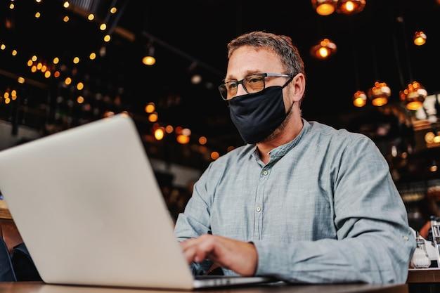 Freelancer met masker over zitten in een café en laptop gebruikt tijdens de uitbraak van het coronavirus.