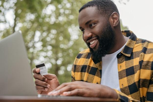 Freelancer ontvangt betaling. african american man met creditcard, met behulp van laptop, online winkelen