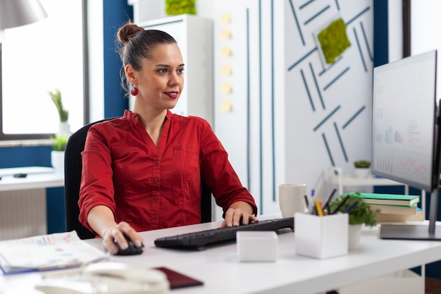 Freelancer op kantoor zit aan bureau te typen op het toetsenbord van de computer