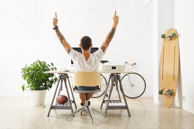 Freelancer op zijn bureaublad met personal computer, omringd door zijn hobbyspeelgoed in lichte kamer voor witte bakstenen muur, strekt zijn armen uit en toont ongecensureerd gebaar