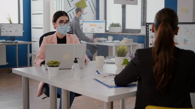 Freelancer praat met collega over zakelijke start terwijl hij in een nieuw, normaal kantoor zit en een beschermend gezichtsmasker draagt om infectie met coronavirus te voorkomen. team respecteert social distancing