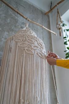 Freelancer vrouw bezig met half afgewerkt macramé stuk, weeft lampenkap voor kroonluchter