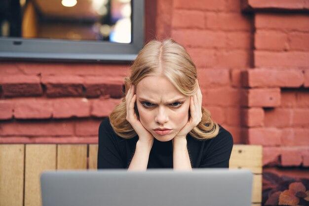 Freelancer vrouw die voor laptop werkt in een café op straat in de buurt van een bakstenen gebouw