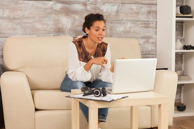 Freelancer vrouw in videoconferentie tijdens het werken vanuit huis zittend op de bank.
