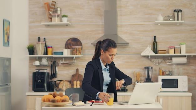 Freelancer vrouw laat op kantoor tijdens het ontbijt. jonge freelancer die de klok rond werkt om haar doelen te bereiken, stressvolle manier van leven, haast, laat op het werk, altijd op de vlucht