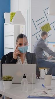 Freelancer werknemer met beschermingsmasker bespreken aan de telefoon voor nieuwe strategie zittend in nieuwe normale co...