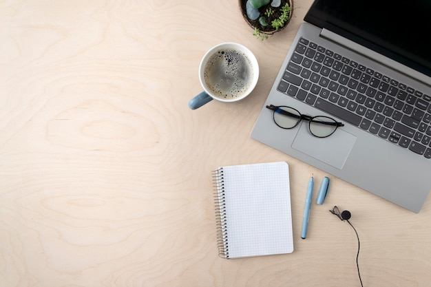 Freelancer werkplek. laptop, koffie, blocnote, microfoon voor het opnemen van lessen op een houten tafel