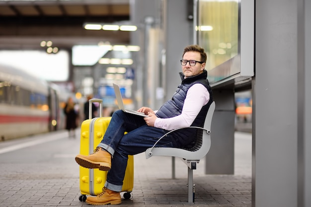 Freelancer werkt met een laptop in een treinstation terwijl hij wacht op transport
