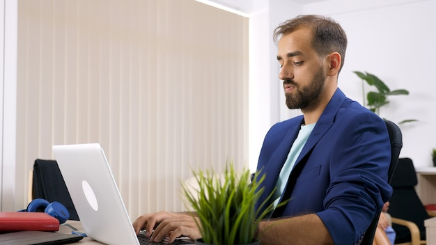 Freelancer zakenman die op de laptop in huis werkt en zijn vrouw is op de achtergrond