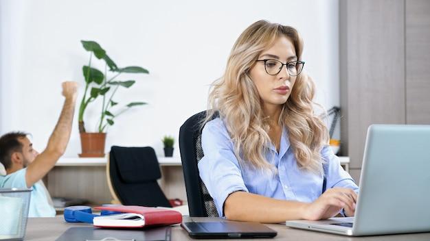 Freelancervrouw die aan de computerlaptop in het huis werkt terwijl de echtgenoot op de achtergrond tv kijkt