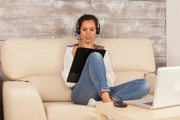Freelancervrouw die een koptelefoon draagt en aantekeningen maakt op het klembord tijdens een videogesprek.