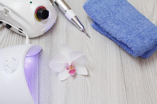Frees, ingeschakeld led uv-lamp en een handdoek op grijze houten achtergrond met orchidee. een set cosmetische hulpmiddelen voor professionele hardware-manicure. bovenaanzicht