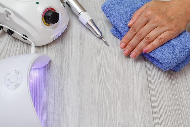 Frees, ingeschakeld led uv-lamp en een vrouwelijke hand op een handdoek op grijze achtergrond. een set cosmetische hulpmiddelen voor professionele hardware-manicure. bovenaanzicht