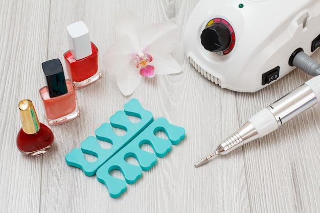Frees, nagellakken en teenscheiders op grijze houten ondergrond. een set cosmetische hulpmiddelen voor professionele hardware-manicure. bovenaanzicht.