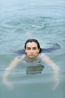 Freestyle zwemmen in de zee in witte zwembroek
