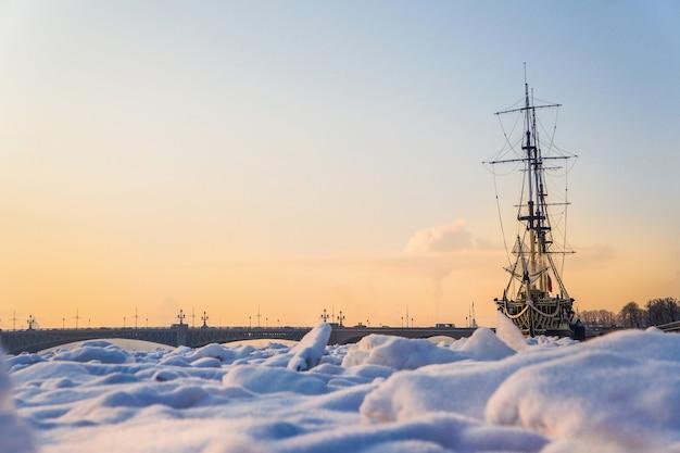 Fregat gebonden door ijs. extreem koud. het concept van wereldwijde koeling. bevroren schip in het ijs op de rivier de neva. sint petersburg.