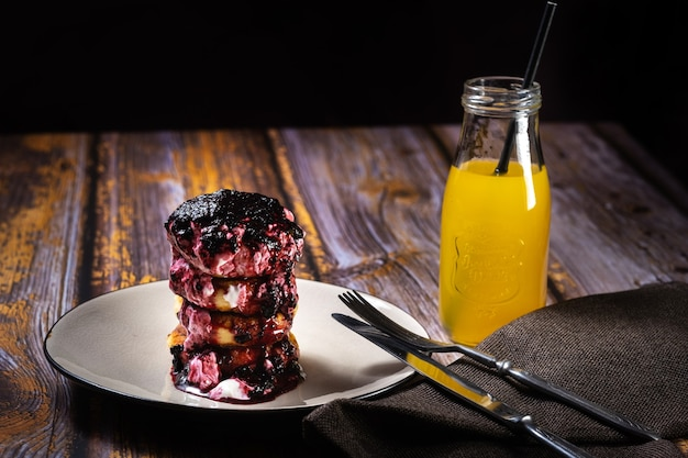 Fried cheesecakes met bosbessenjam en zure room op een bord met sinaasappelsap in een fles