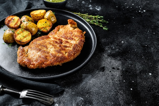 Fried chicken-schnitzel met gebakken aardappels.