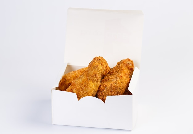 Fried chicken wings in kartonnen doos op witte ondergrond