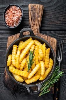 Fried crinkle frieten aardappelen in een pan. zwarte houten achtergrond. bovenaanzicht.