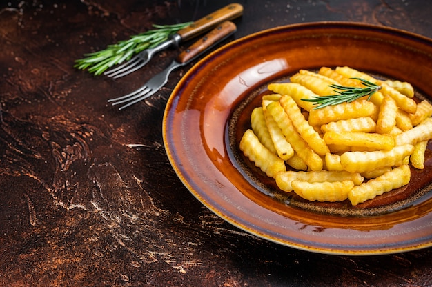 Fried crinkle frieten aardappelen of chips in een rustieke plaat. donkere achtergrond. bovenaanzicht. ruimte kopiëren.