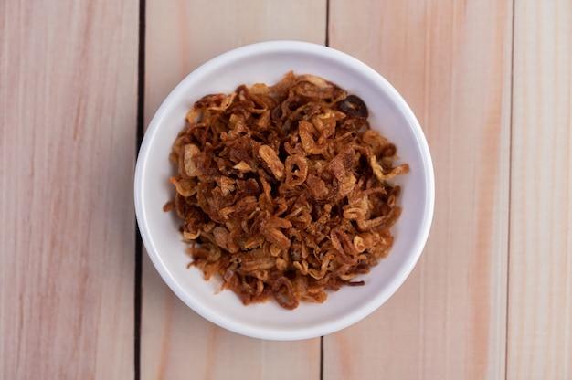 Fried onion op een witte plaat op een houten vloer.