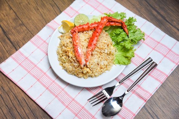 Fried rice-krabzeevruchten op napery / gezonde voedsel gebraden rijst met krabbenen met eicitroen en komkommer op witte plaat houten lijst