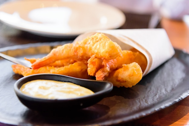 Fried shrimp met mayonaise op zwarte plaat.