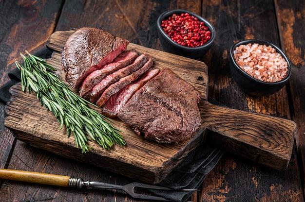Fried top blade of platte ijzeren rosbief vlees steaks op een houten bord met rozemarijn