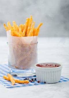 Frieten aardappelchips in glas met tomatenketchup en peper op blauw restaurantpapier en lichte achtergrond