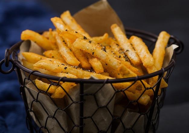 Frieten chips in snack emmer op zwarte stenen bord met blauwe handdoek op donkere achtergrond. macro