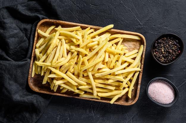 Frieten in een houten kom. biologische aardappelen. zwarte achtergrond. bovenaanzicht