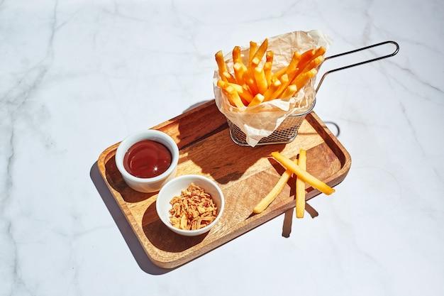 Frieten in een metalen mand op houten dienblad met saus en friet in fel zonlicht fastfood concept