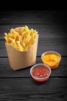 Frieten in een papieren mand. fast food. franse frietjes in een kartonnen doos met saus op zwarte achtergrond. kopieer ruimte