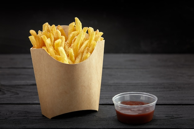 Frieten in een papieren mandje. fast food. franse frietjes in een papieren doos op zwarte achtergrond