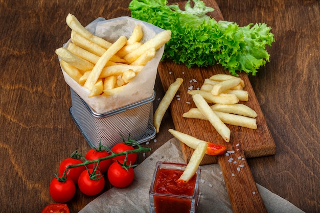 Frieten in een rooster met ketchup, salade en cherrytomaatjes op houten bruine tafel